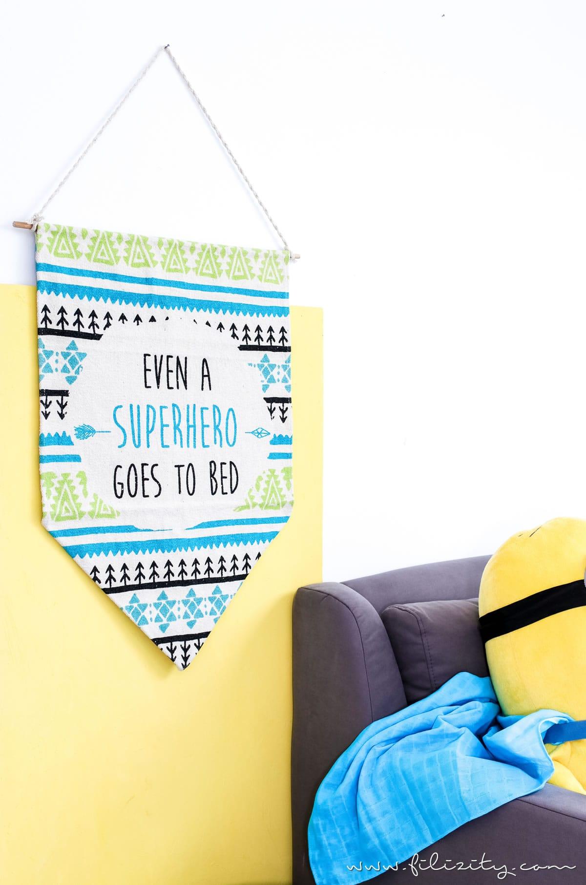 Wimpel aus buntem Teppich vor gelbem Hintergrund mit Minion auf der Couch | Kinderzimmer-Deko selber machen: DIY Wimpel aus Teppich | Filizity.com | DIY-Blog aus dem Rheinland #kinderzimmer #kinder #superhelden