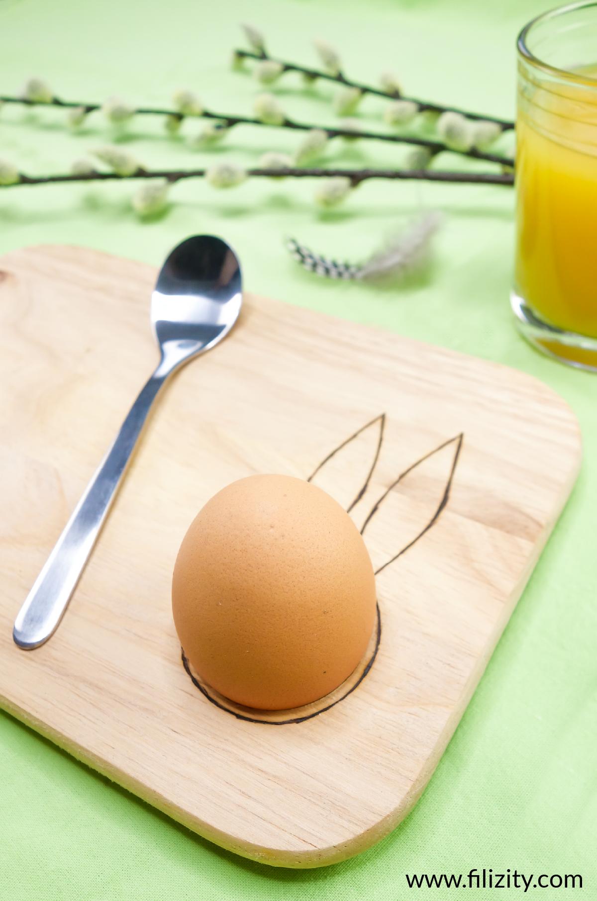 Selbst gemachtes Oster-Frühstücksbrett mit Eierbecher und Hasenohren Brandmalerei, ein Frühstücksei, ein Metalllöffel und ein Glas Orangensaft | Filizity.com - Kreativmagazin &DIY Blog